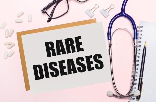 淡いピンクの背景に、聴診器、紙用の白い丸薬とクリップ、黒いフレームの眼鏡、「希少疾患」というテキストが書かれた一枚の紙。上からの眺め。医療の概念