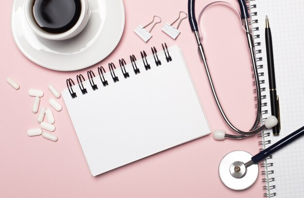 淡いピンクの背景に、白い一杯のコーヒー、白い錠剤、聴診器、ペン、テキストやイラストを挿入する場所のある白いメモ帳。