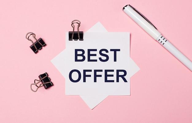 На светло-розовом фоне черные скрепки, белая ручка и белая бумага для заметок с текстом best offer. плоская планировка