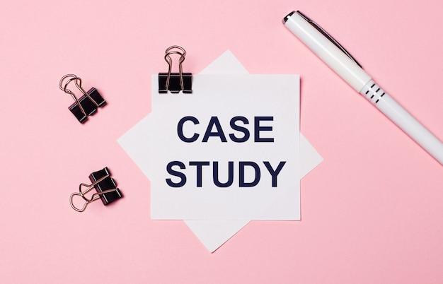 На светло-розовом фоне черные канцелярские скрепки, белая ручка и белая бумага для заметок с текстом практическое исследование. плоская планировка