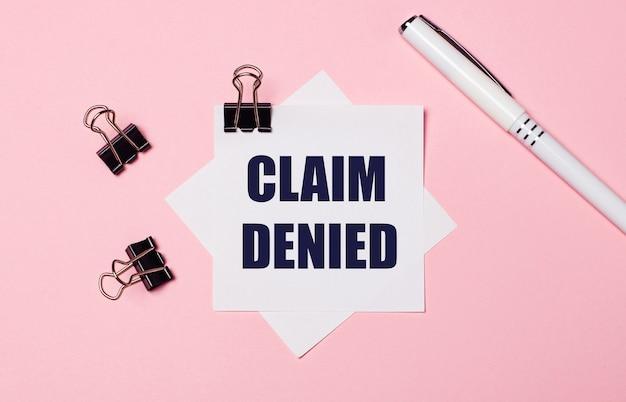 На светло-розовом фоне черные скрепки, белая ручка и белая бумага для заметок с текстом претензия отказана. плоская планировка