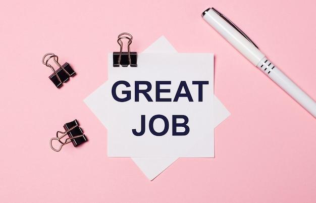 На светло-розовом фоне черные скрепки, белая ручка и белая бумага для заметок с текстом great job. плоская планировка