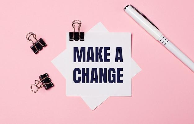 На светло-розовом фоне черные канцелярские скрепки, белая ручка и белая бумага для заметок с текстом внести изменение. плоская планировка