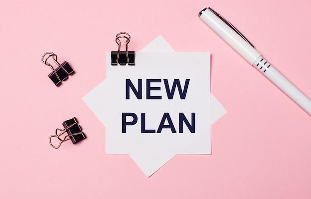На светло-розовом фоне черные скрепки, белая ручка и белая бумага для заметок с текстом new plan. плоская планировка