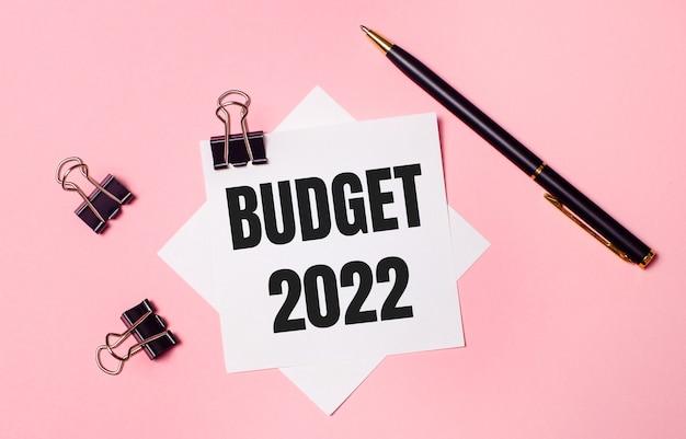 На светло-розовом фоне черные скрепки, черная ручка и белая бумага для заметок с надписью budget 2022. flat lay