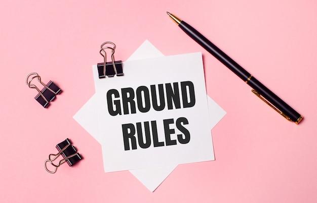 На светло-розовом фоне черные канцелярские скрепки, черная ручка и белая бумага для заметок со словами общие правила. плоская планировка