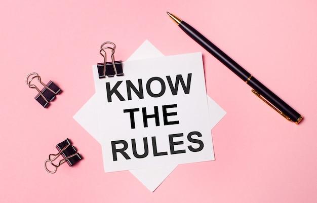 На светло-розовом фоне черные скрепки, черная ручка и белая бумага для заметок со словами «знайте правила». плоская планировка