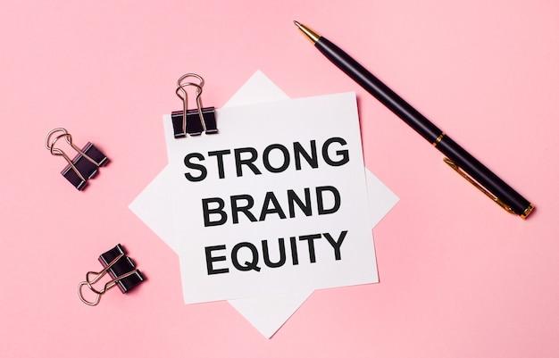 На светло-розовом фоне черные скрепки, черная ручка и белая бумага для заметок с надписью strong brand equity. плоская планировка