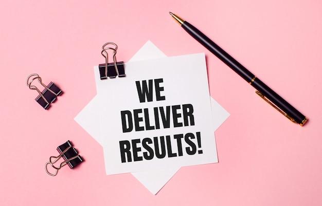 На светло-розовом фоне черные скрепки, черная ручка и белая бумага для заметок с надписью «мы доставляем результаты». плоская планировка