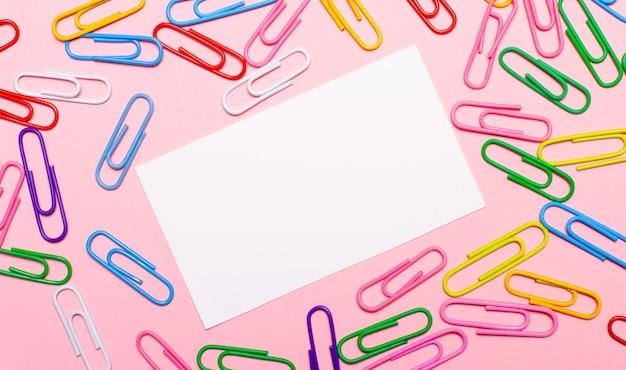 明るいピンクの背景に、カラフルな明るいペーパークリップと、中央にテキストを挿入する場所のある白い空白のカード。レンプレート。コピースペース