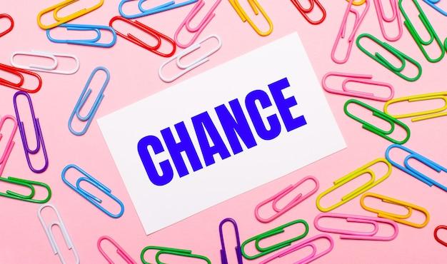 На светло-розовом фоне разноцветные яркие скрепки и белая открытка с текстом шанс.
