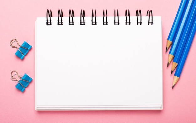 明るいピンクの背景に、水色の鉛筆とペーパークリップ、テキストを挿入するスペースのある白い空白のノートブック。レンプレート