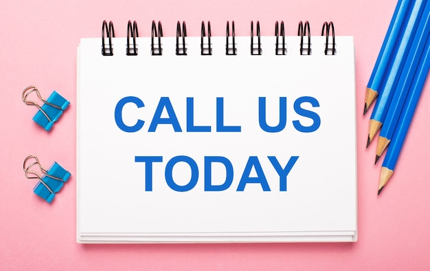 明るいピンクの背景に、水色の鉛筆、ペーパークリップ、白いノートに「call ustoday」というテキストが表示されます