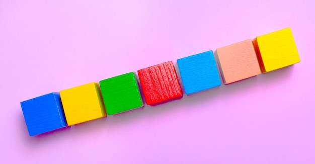 淡いピンクの背景に、テキストを挿入する場所のあるマルチカラーの木製の立方体。