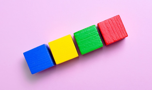 밝은 분홍색 배경에 텍스트를 삽입할 수 있는 여러 색상의 나무 큐브.