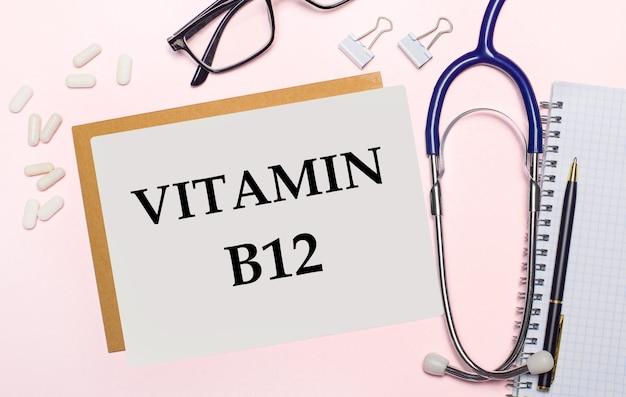 淡いピンクの表面に、「ビタミンb12」というテキストが書かれた一枚の紙。上からの眺め。医療の概念。
