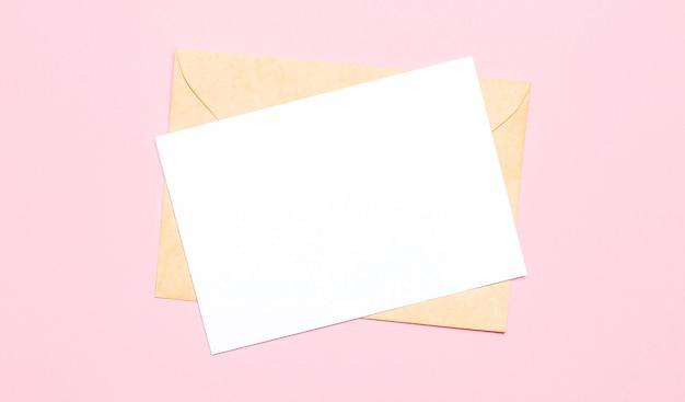 淡いピンクの壁、封筒、テキストやイラストを挿入する場所のある空白のカード。上から見る