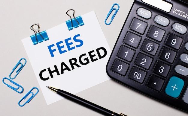 밝은 표면에 계산기, 펜, 파란색 종이 클립 및 fees charged라는 텍스트가있는 종이