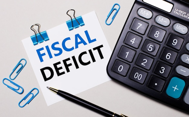На светлой поверхности калькулятор, ручка, синие канцелярские скрепки и лист бумаги с текстом fiscal deficit.