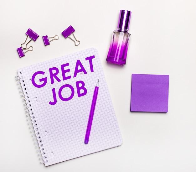 На светлой поверхности - сиреневый подарок, духи, сиреневые деловые аксессуары и блокнот с лиловой надписью great job. плоская планировка. женская бизнес-концепция