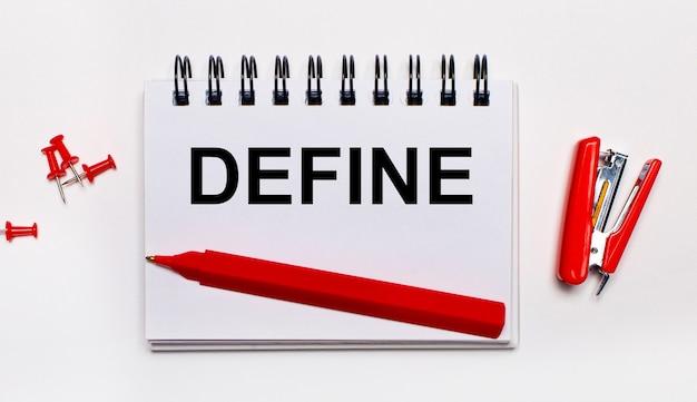 На светлой поверхности красная ручка, красный степлер, красные скрепки и блокнот с надписью define.