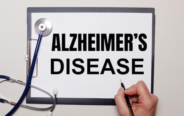 На светлой поверхности стетоскоп и лист бумаги, на котором мужчина пишет: «альцгеймер - это болезнь».