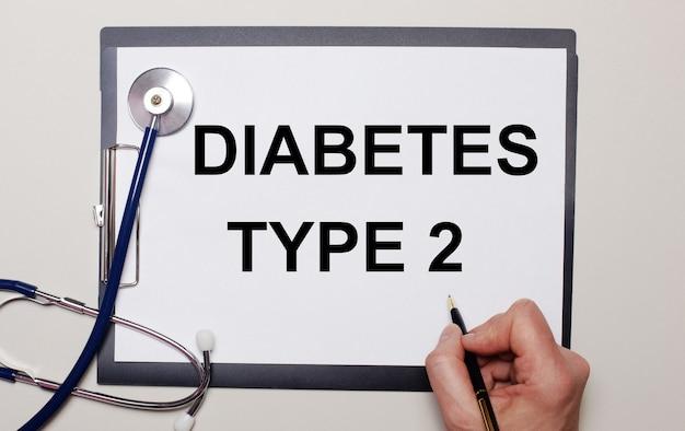 На светлой поверхности стетоскоп и лист бумаги, на котором мужчина пишет диабет типа 2. медицинское понятие.