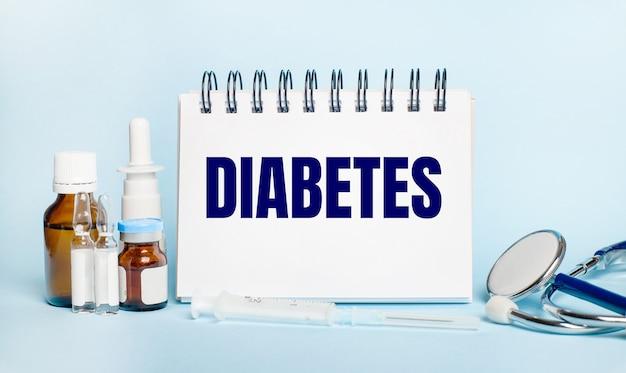 На светлой поверхности шприц, стетоскоп, пузырьки с лекарством, ампула и белый блокнот с надписью diabetes.