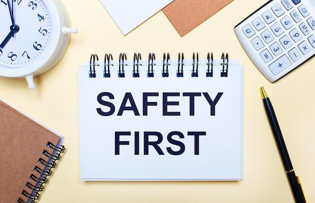明るい場所に、白い目覚まし時計、電卓、ペン、そして「安全第一」というテキストのノート