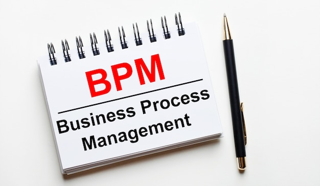 明るい表面に、bpmビジネスプロセス管理という言葉とペンが付いた白いノート。
