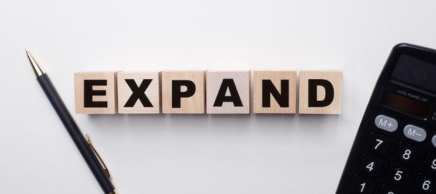 電卓とペンの間の明るい面には、expandという単語が付いた木製の立方体があります。