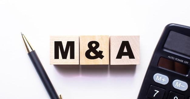 계산기와 펜 사이의 밝은 표면에는 m and a라는 단어가있는 나무 큐브가 있습니다.