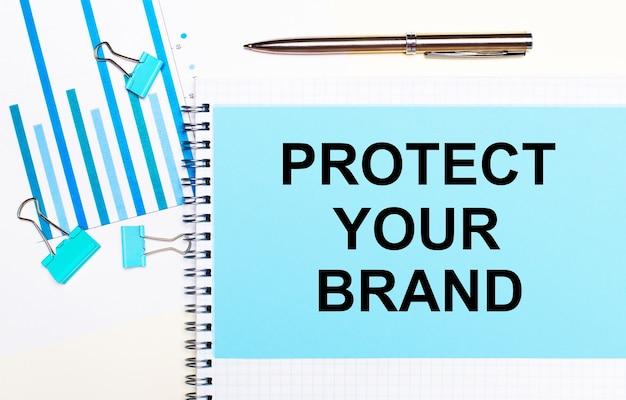 На светлой поверхности голубые схемы, скрепки и лист бумаги с текстом защищайте свой бренд. вид сверху. бизнес-концепция
