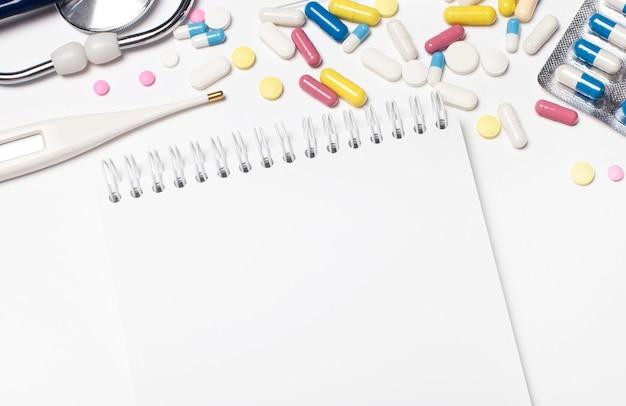 На светлой поверхности разноцветные таблетки, стетоскоп, электронный градусник и чистый блокнот с местом для вставки текста.