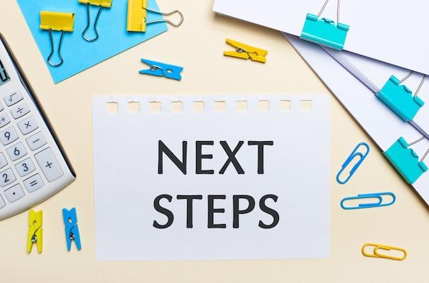 明るい面には、書類の山、白い電卓、黄色と青のペーパークリップと洗濯バサミ、そして「次のステップ」というテキストが書かれたノートがあります。