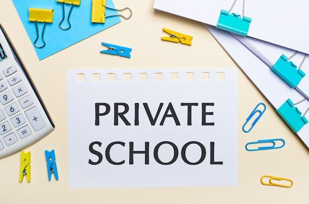밝은 표면에는 문서 더미, 흰색 계산기, 노란색 및 파란색 종이 클립과 빨래 집게, 텍스트가 private school 인 노트북이 있습니다.