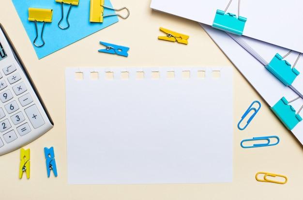밝은 표면에는 계산기, 노란색 및 파란색 종이 클립, 빨래 집게, 문서 및 텍스트를 삽입 할 빈 종이가 있습니다. 평평하다. 텍스트를 삽입 할 위치입니다.