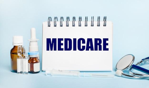 ライトテーブルには、注射器、聴診器、薬瓶、アンプル、メディケアと書かれた白いメモ帳があります。医療の概念