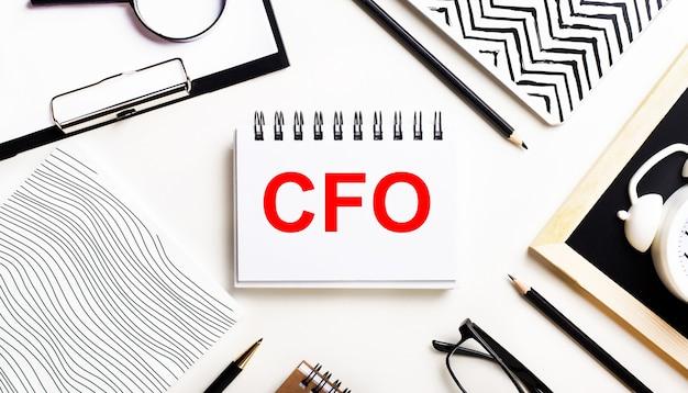 На светлом столике тетради, увеличительное стекло, будильник, очки и ручка. а в центре - блокнот с текстом cfo chief financial officer.