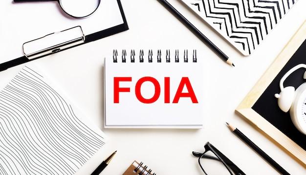 На светлом столике тетради, увеличительное стекло, будильник, очки и ручка. а в центре блокнот с текстом foia the freedom of information act.