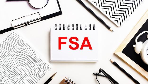 На светлом столике тетради, увеличительное стекло, будильник, очки и ручка. а в центре - блокнот с текстом fsa flexible spending account.