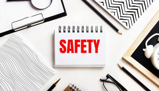 На светлом столике тетради, увеличительное стекло, будильник, очки и ручка. а в центре блокнот с надписью безопасность.