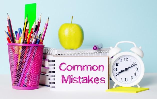 가벼운 탁자에는 책, 문구류, 흰색 자명종, 사과가 있습니다. 그 옆에는 common misakes라는 문구가 적힌 공책이 있습니다. 교육 개념입니다.