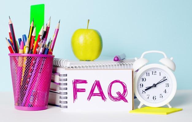 На светлом столике книги, канцелярские товары, белый будильник, яблоко. рядом находится блокнот с текстом faq. образовательная концепция.