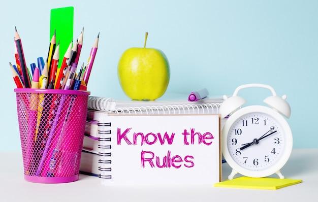 На светлом столике книги, канцелярские товары, белый будильник, яблоко. рядом лежит блокнот с надписью знай правила. образовательная концепция.
