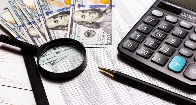 На светлом столике - доллары, увеличительное стекло, ручка и калькулятор. крупный план на рабочем месте. бизнес-концепция
