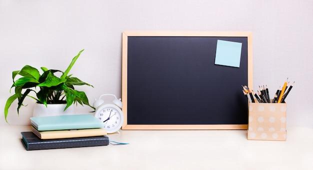 ライトテーブルには、黒板、白い目覚まし時計、メモ帳、鉛筆、鉢植えの植物があります。ホームオフィスのコンセプト。スペースをコピーします。ビジネスコンセプト