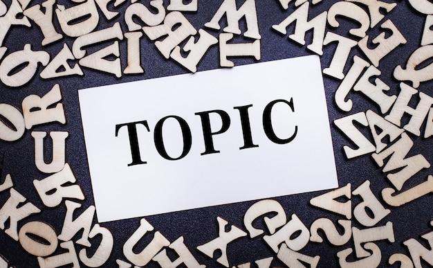 ライトテーブルの上に、英語のアルファベットの木製の文字と、トピックという単語が入った白いカードがあります。