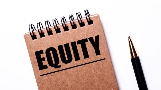 明るい壁に、黒いペンと黒いバネに「equity」と刻まれた茶色のノート