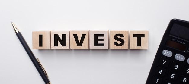 계산기와 펜 사이의 밝은 벽에는 invest라는 단어가있는 나무 큐브가 있습니다. 금융 개념